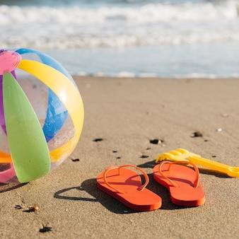 Slippers en opblaasbare bal in het zand op het strand