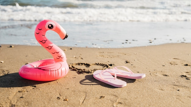 Slippers en opblaasbare flamingo op het strand