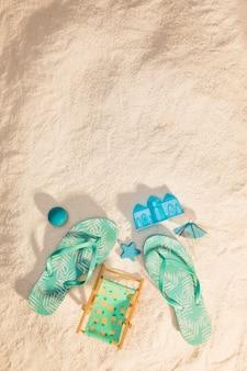 Slippers en zandspeelgoed op het strand
