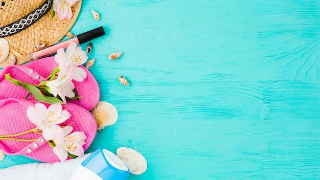 Slippers in de buurt van hoed tussen bloemen met schelpen en lippenstift