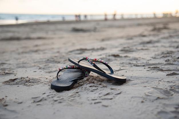 Slippers op het strand met zandstrand zonsondergang en oceaan zee