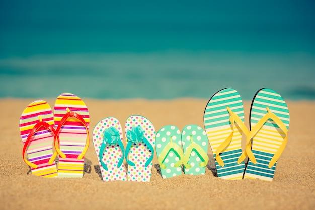 Slippers op zandstrand tegen blauwe zee en lucht and