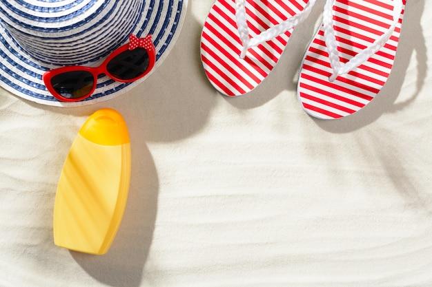 Slippers, zonnebrandcrème, zonnebril en hoed op het zand, bovenaanzicht