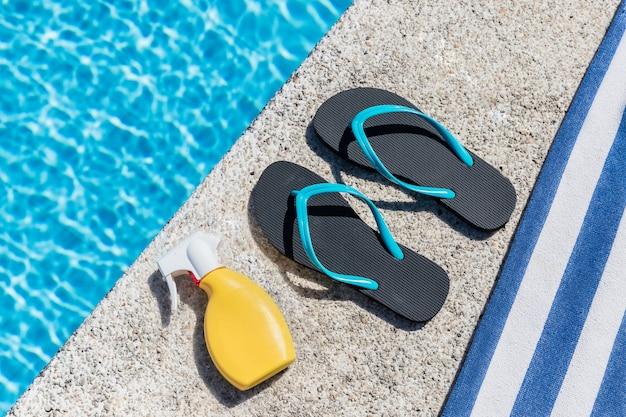 Slippers, zonnespray en een handdoek aan de rand van een zwembad. kopieer ruimte. bovenaanzicht.