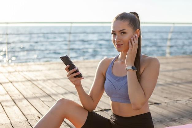 Slm fitte vrouw in sportkleding gebruikt een smartphone en luistert naar muziek met een koptelefoon terwijl ze bij zonsopgang op een mat op het strand zit