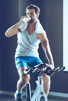 Slokje vers water na een geweldige training. jonge knappe man in sportkleding drinkwater tijdens het fietsen in de sportschool