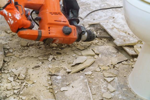 Sloop van oude tegels met jackhammer. renovatie van de oude vloer.