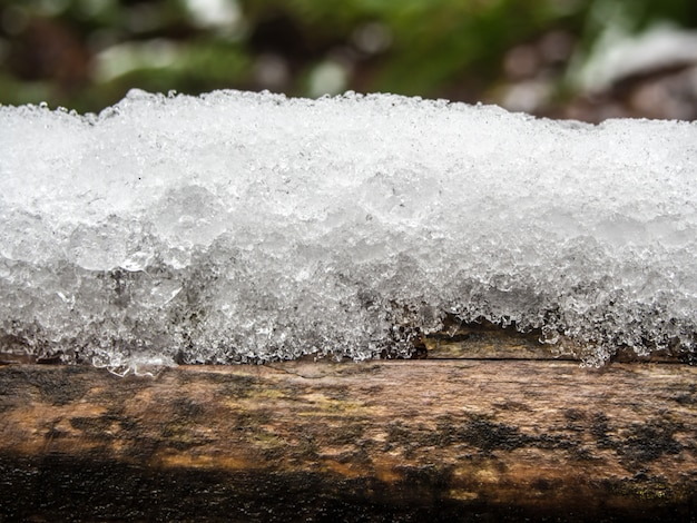 Sloot ijs van sneeuw op hout