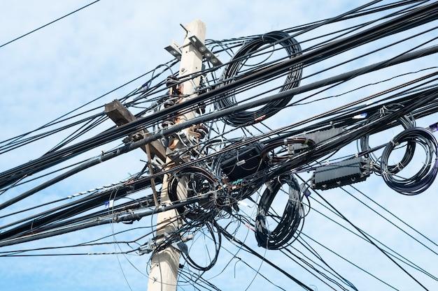 Slordige elektrische kabels in thailand - vele lijnen van kabels chaotische reeks verweven, optische vezeltechnologie openlucht in openlucht.