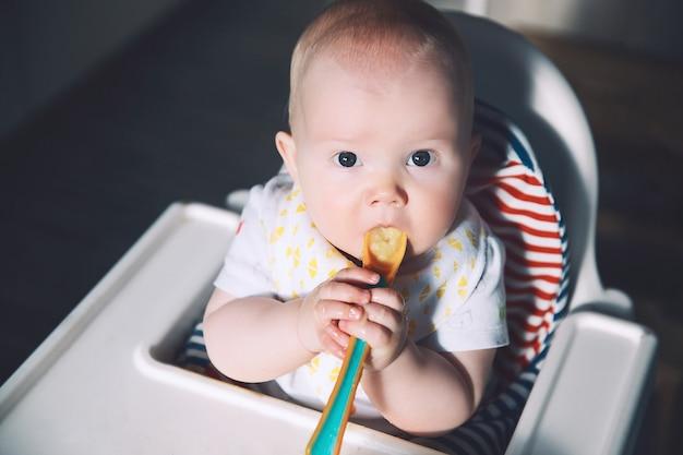 Slordige lachende baby voeden die met een lepel in de kinderstoel eet baby's eerste vaste voedsel