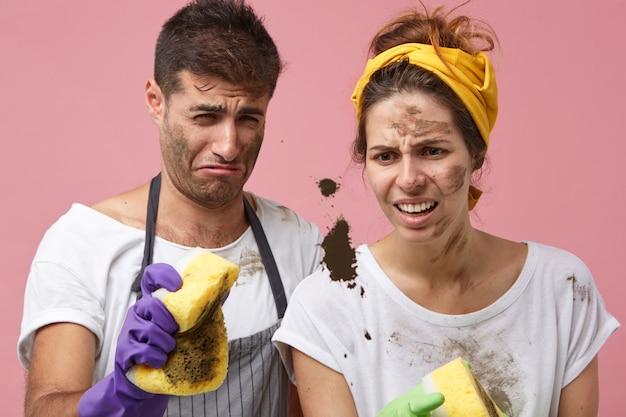 Slordige mannen en vrouwen die hun huis klusjes doen, ramen schoonmaken en met een walgelijke blik naar zwarte vlek kijken en proberen het met sponzen weg te vegen. mensen, huishouden, huishoudelijk werk, huishoudelijk concept