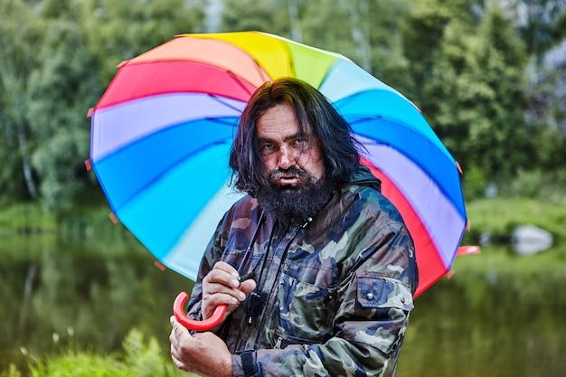 Slordige ruige man, 53 jaar oud, met een geschilderde baard en pruilende lippen, verbergt zich voor regen onder een regenboogparaplu.