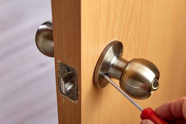 Slotenmaker draait deurklink los om het slot te repareren.