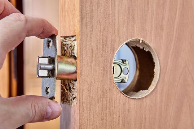 Slotenmaker duwt de vergrendeling tijdens de installatie door het gat op de nieuwe deur