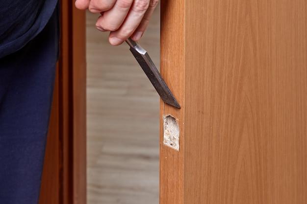 Slotenmaker gebruikt een houtbeitel om de uitsparing voor de deurvergrendelingsplaat uit te steken