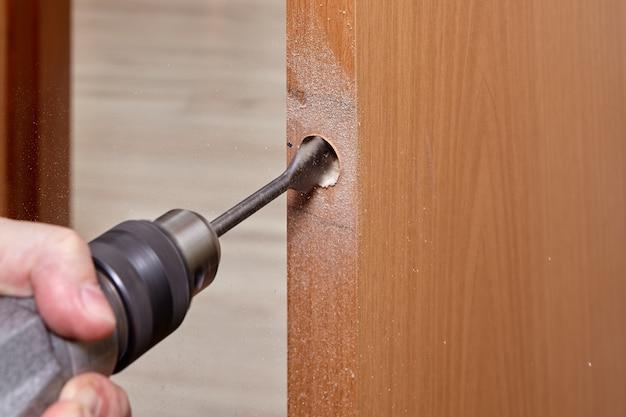 Slotenmaker gebruikt een platte bit om hout te boren bij het boren van een gat voor vergrendeling.