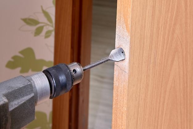 Slotenmaker gebruikt een platte bit om hout te boren bij het boren van een gat voor vergrendeling