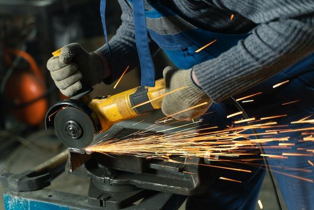 Slotenmaker in speciale kleding en bril werkt in productie. metaalbewerking met haakse slijper