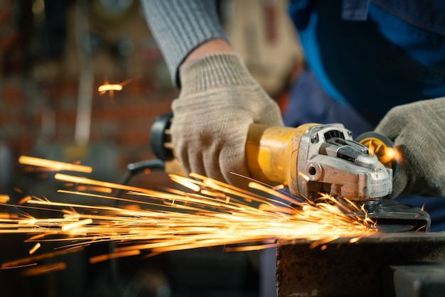 Slotenmaker in speciale kleding en bril werkt in productie metaalverwerking met haakse slijper