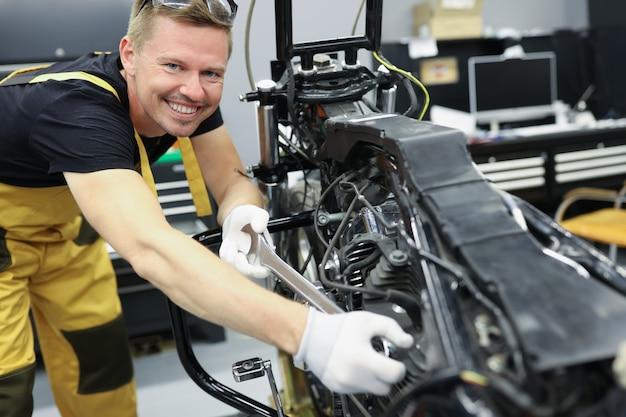 Slotenmaker monteur met moersleutel staat naast motorfiets motor motorfiets reparatie concept