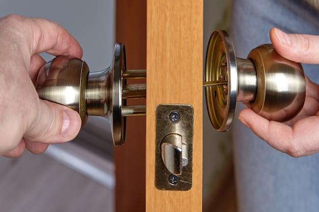 Slotenmaker verbindt twee delen van de deurklink door de sluiter in het gat te duwen.