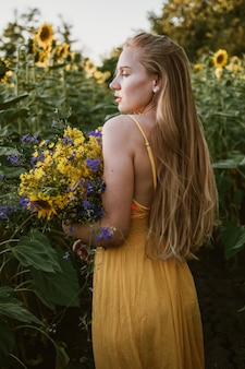 Slow living concept nieuwe lifestyle trend. ontspannende jonge vrouw met bloemen in de natuur