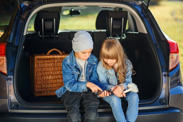Slow motion van blond 12-jarige meisje en knappe 10-jarige jongen in jeans kleding die in de kofferbak zitten en kijken op zijn smartphone
