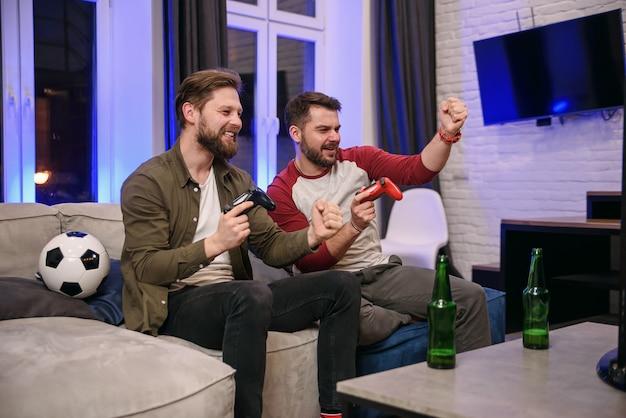 Slow motion van emotioneel opgewonden grappige jonge multi-etnische jongens die met elkaar voor de gek houden tijdens het spelen van videogames