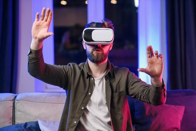 Slow motion van sympathieke vrolijke positieve man met baard die werkt op het denkbeeldige touchscreen in augmented reality-bril