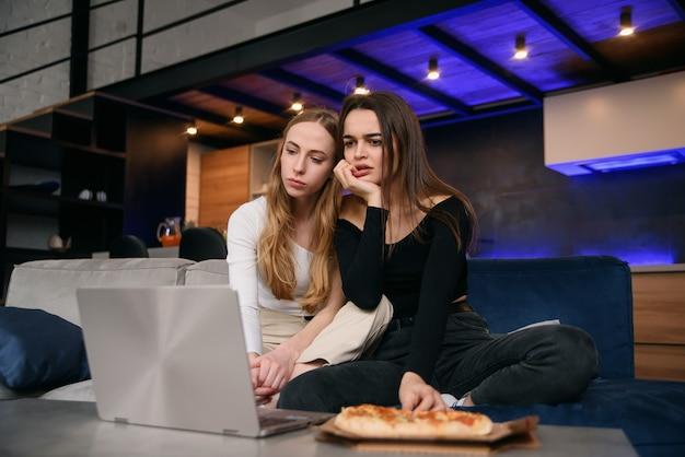 Slow motion van verrast aantrekkelijke 25s stijlvolle vriendinnen die op de comfortabele bank zitten en genieten van heerlijke pizza tijdens het bladeren door grappige foto's op de computer