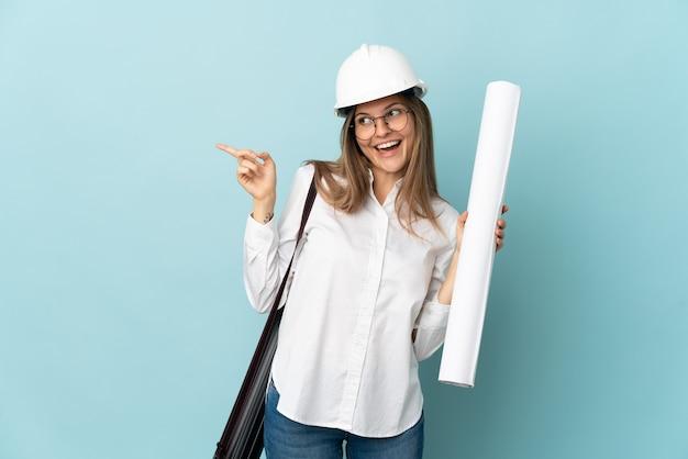 Slowaaks architectenmeisje die blauwdrukken houden die op blauwe muur worden geïsoleerd die vinger aan de kant richten en een product voorstellen