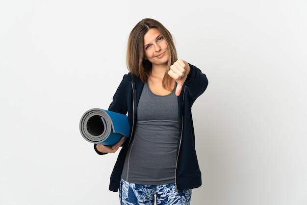 Slowaaks meisje dat naar yogalessen gaat die op witte achtergrond worden geïsoleerd die duim met negatieve uitdrukking toont