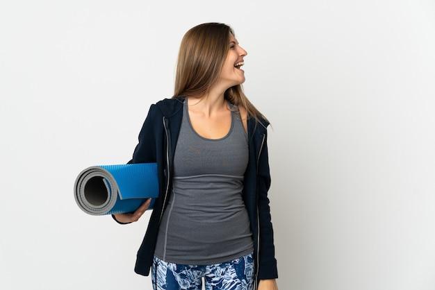 Slowaaks meisje dat naar yogalessen gaat die op witte achtergrond worden geïsoleerd die in zijpositie lachen