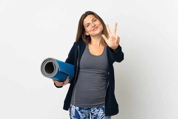 Slowaaks meisje dat naar yogalessen gaat die op witte muur gelukkig worden geïsoleerd en drie met vingers tellen