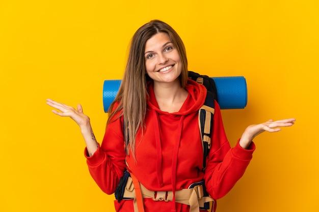 Slowaakse bergbeklimmervrouw met een grote rugzak die op gele achtergrond met geschokte gezichtsuitdrukking wordt geïsoleerd