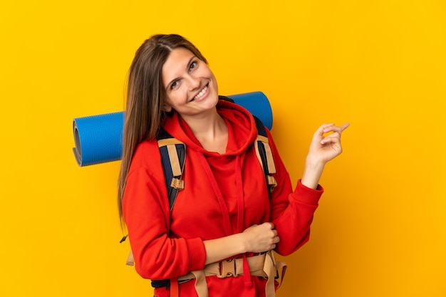 Slowaakse bergbeklimmervrouw met een grote rugzak geïsoleerd op een gele achtergrond die met de vinger naar de zijkant wijst