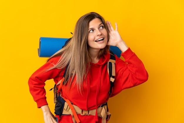 Slowaakse bergbeklimmervrouw met een grote rugzak geïsoleerd op een gele achtergrond die naar iets luistert door de hand op het oor te leggen
