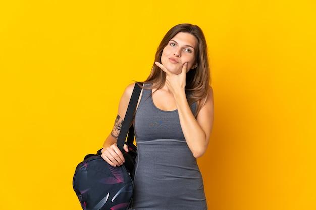 Slowaakse sportvrouw met sporttas die bij het gele muur denken wordt geïsoleerd