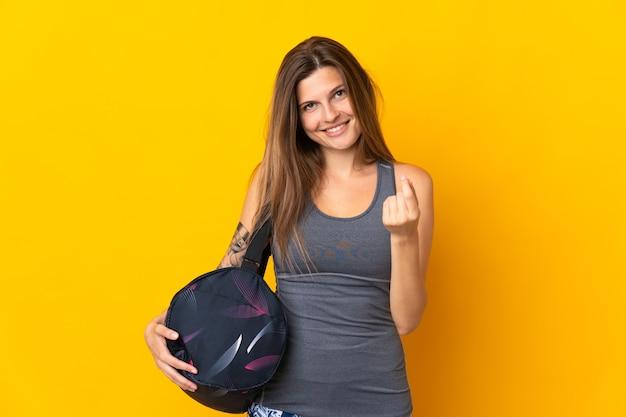 Slowaakse sportvrouw met sporttas die op gele achtergrond wordt geïsoleerd die geldgebaar maakt