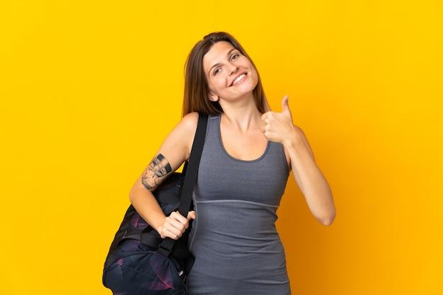 Slowaakse sportvrouw met sporttas geïsoleerd op gele achtergrond met duimen omhoog omdat er iets goeds is gebeurd