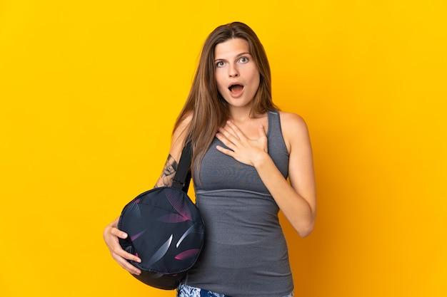 Slowaakse sportvrouw met sporttas geïsoleerd op gele achtergrond verrast en geschokt terwijl ze naar rechts kijkt