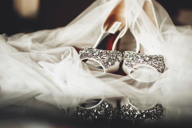 Sluier bedekt bruidsschoenen rijkelijk versierd met zilver en kristallen