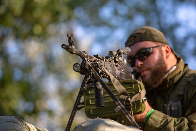 Sluipschutter gewapend met groot kaliber, sluipschuttergeweer, schietende vijandelijke doelen op bereik van schuilplaats, zittend in een hinderlaag