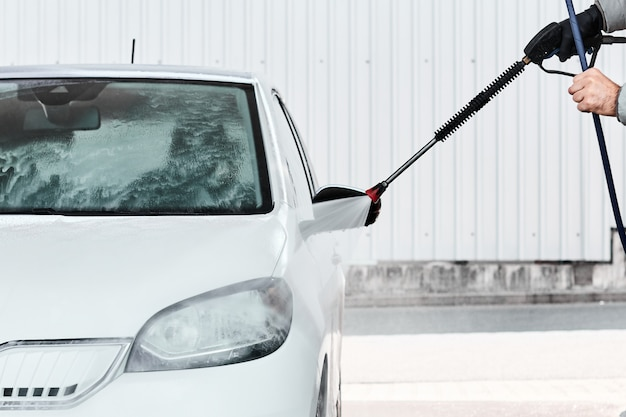 Sluit bemant omhoog hand die een witte auto wassen gebruikend hogedrukwater. zelf wassen van auto's