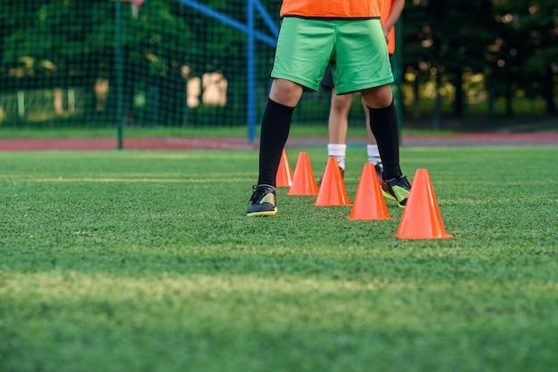 Sluit de benen van de voetballer die tussen plastic oranje kegels lopen die op kunstmatig stadion staan