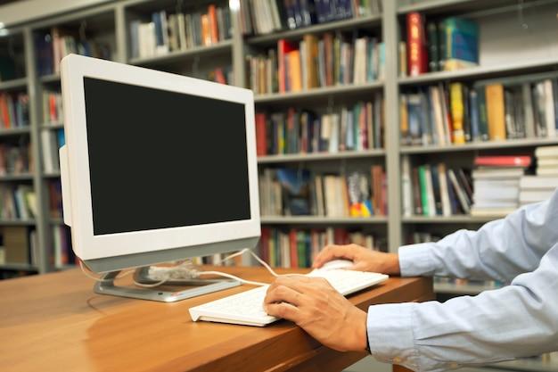 Sluit de blanco van het beeldscherm met de hand van een man die computers op het bureau gebruikt