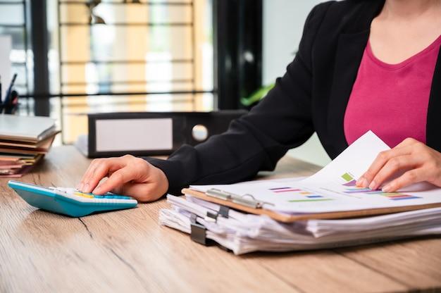Sluit de hand van zakenvrouw met behulp van de huishoudelijke financiën van rekenmachines of belastingen op machine-, financiële en boekhoudkundige concepten,