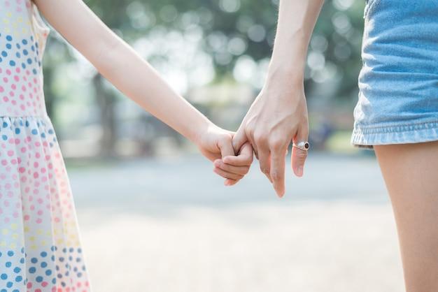 Sluit de handholding van de dochter met haar moeder, voel me getroost en aanhankelijk, gelukkige familietijd