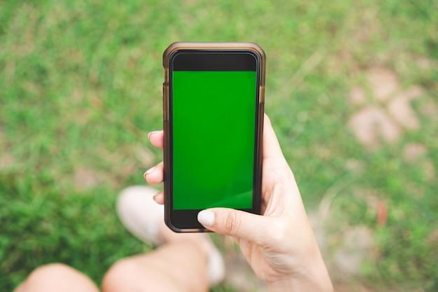 Sluit de holdingssmartphone van de vrouwenhand met het lege groene exemplaar ruimtescherm.