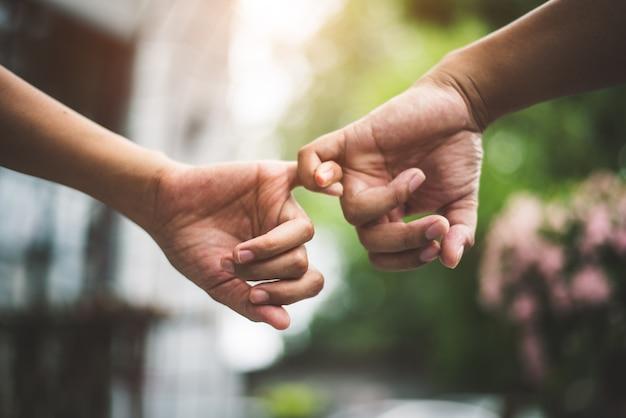 Sluit de pinkiesvingers van het paarholding in park zoals zweer en beloof gebaar in huwelijksce